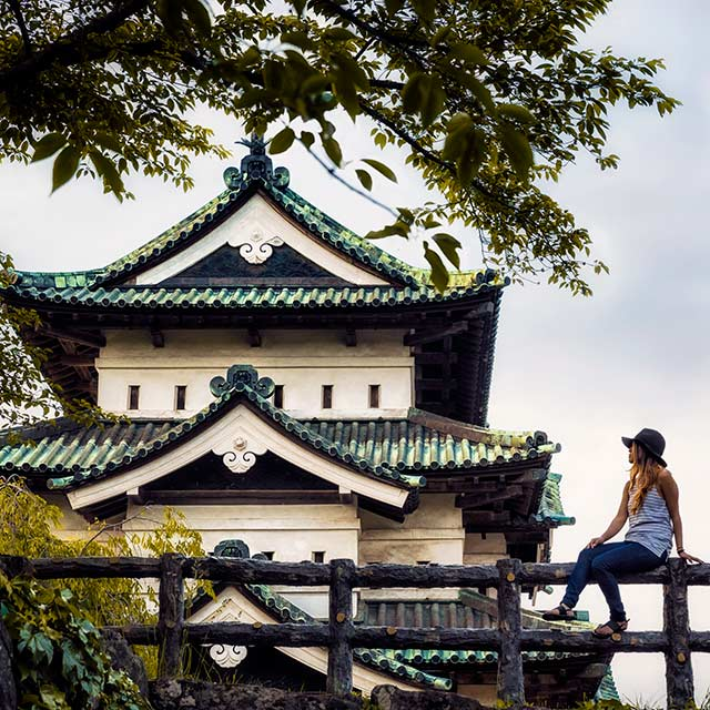 woman sits on fence in front of Hirosaki Castle in Aomori, Japan